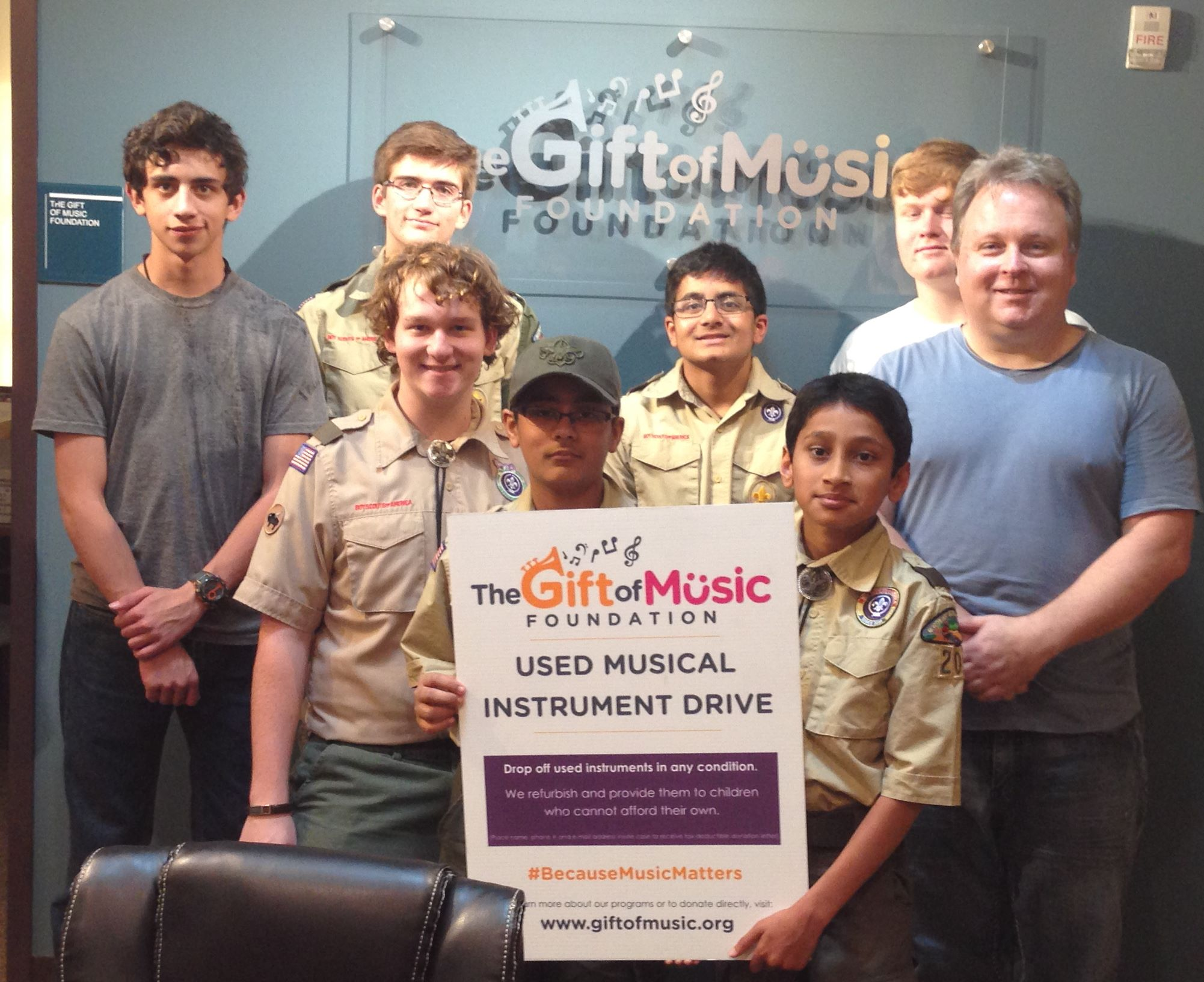 Scouts and Gift of Music Executive Director Chris Monroe celebrate instrument drive